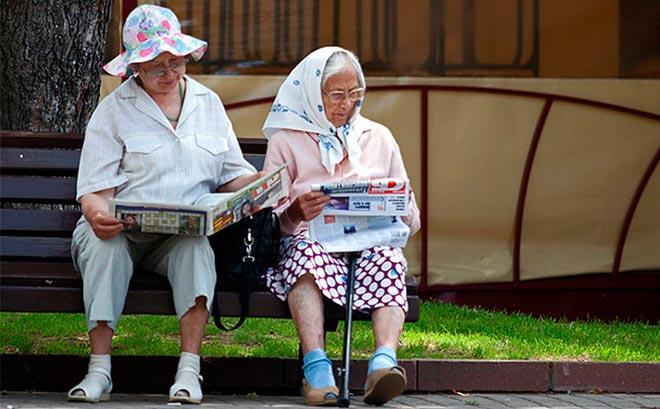 Бабушки на скамейке читают газету