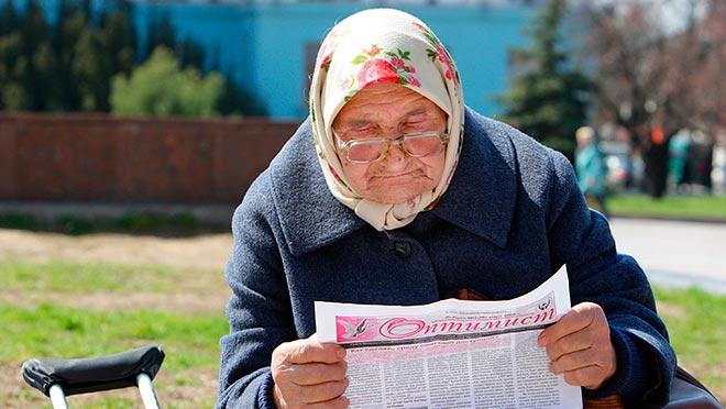 Бабушка на скамейке читает газету